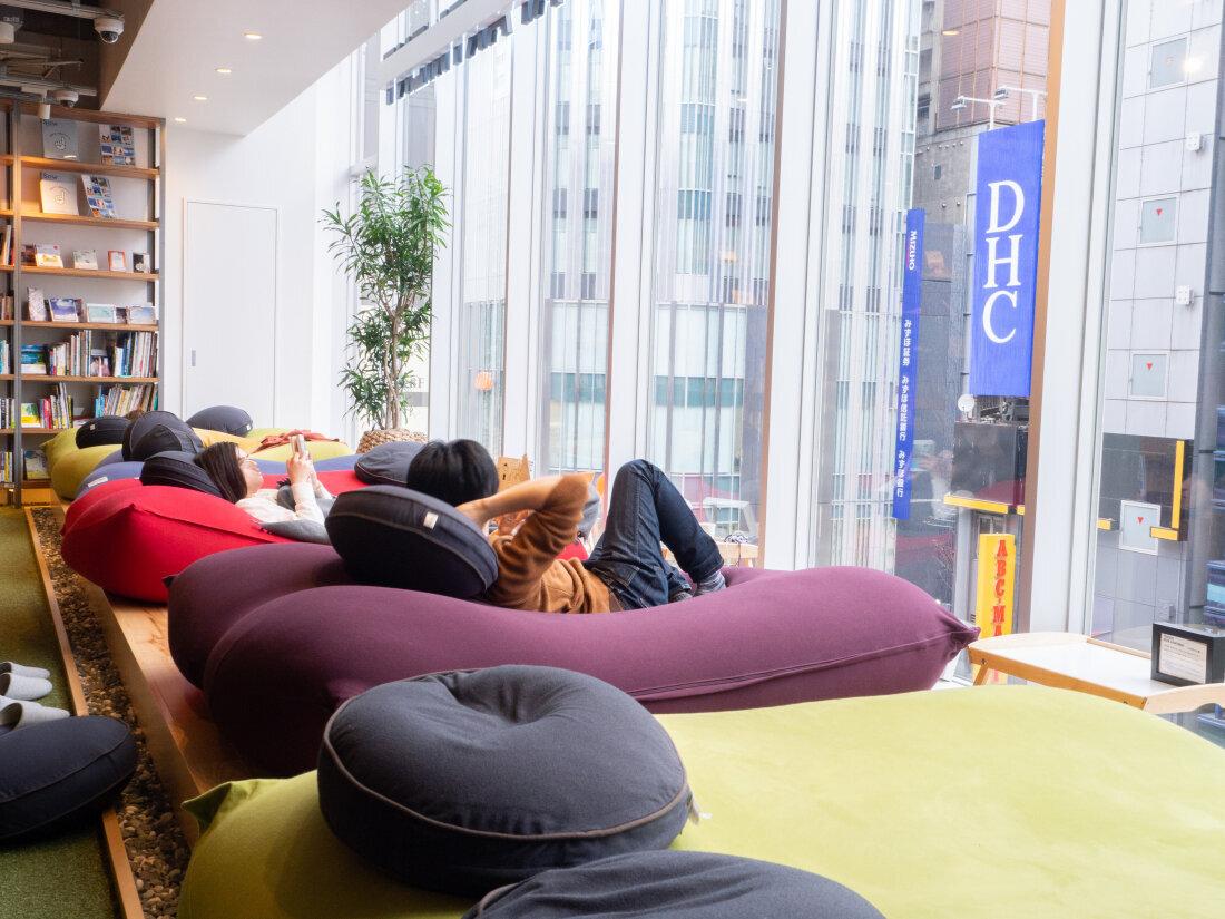 草地旁落地窗一側,有一排大懶人椅,客人們一個個舒服地躺著,非常愜意。