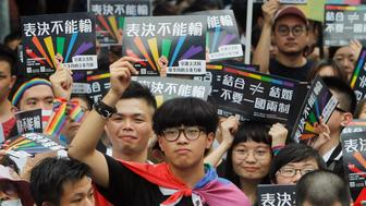 Same-sex marriage supporters gather outside the Legislative Yuan in Taipei, Taiwan, Friday, May 17, 2019. Taiwan's Constitutional Court is scheduled to decide Friday on legalizing same-sex marriage, marking a potential first in Asia. The signs read  ''Vote Can't Be Defeated.'' (AP Photo/Chiang Ying-ying)