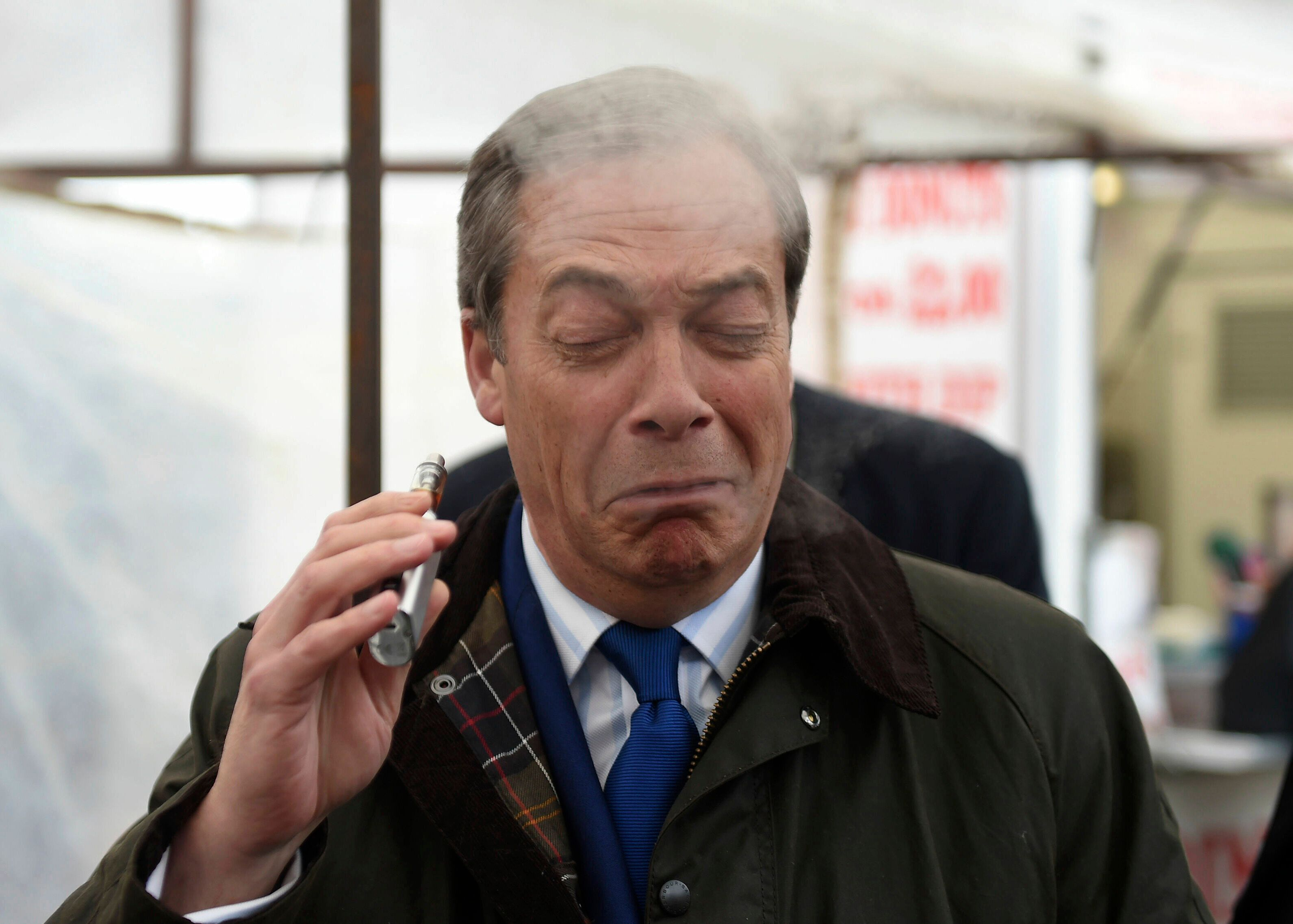 Brexit Party leader Nigel Farage coughs as he samples a Pinkman flavoured e-cigarette during a Brexit Party walkabout in Lincoln, England, Friday May 10, 2019. (Joe Giddens/PA via AP)
