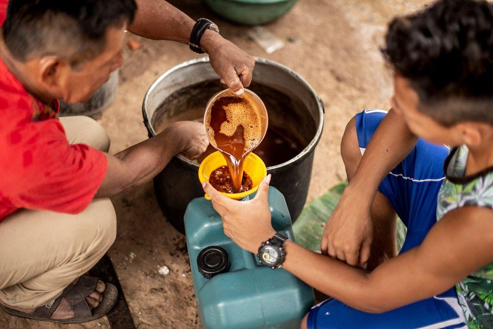 Un chamán vierte la ayahuasca en una garrafa en Pucallpa,