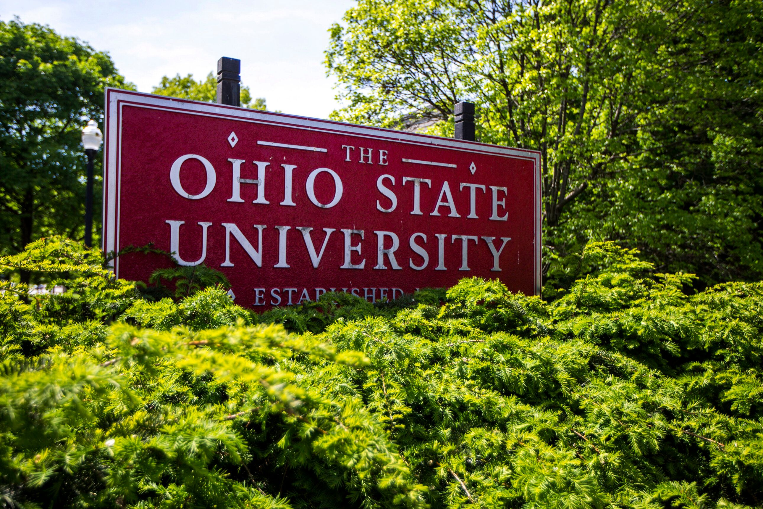 This May 8, 2019 photo shows a sign for Ohio State University in Columbus, Ohio. On Friday, May 17, 2019, the school said at least 177 men were sexually abused by Ohio State team doctor Richard Strauss who died years ago, according to findings from a law firm that investigated the accusations, concluding that school leaders knew at the time. (AP Photo/Angie Wang)