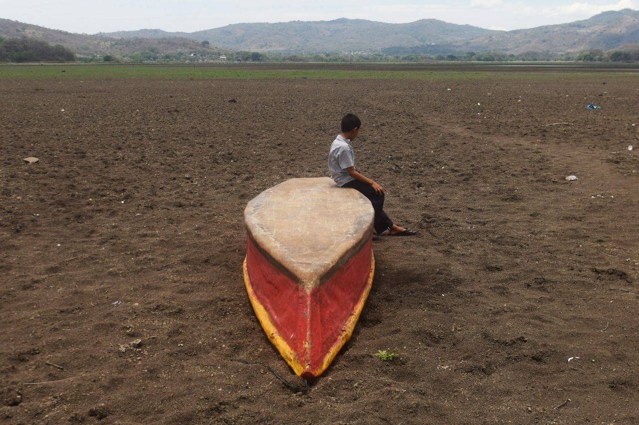 In a photo from May 2017, a boy sits on an abandoned boat on what is left of Guatemala's Lake Atescatempa, which dried up due to drought and high temperatures.