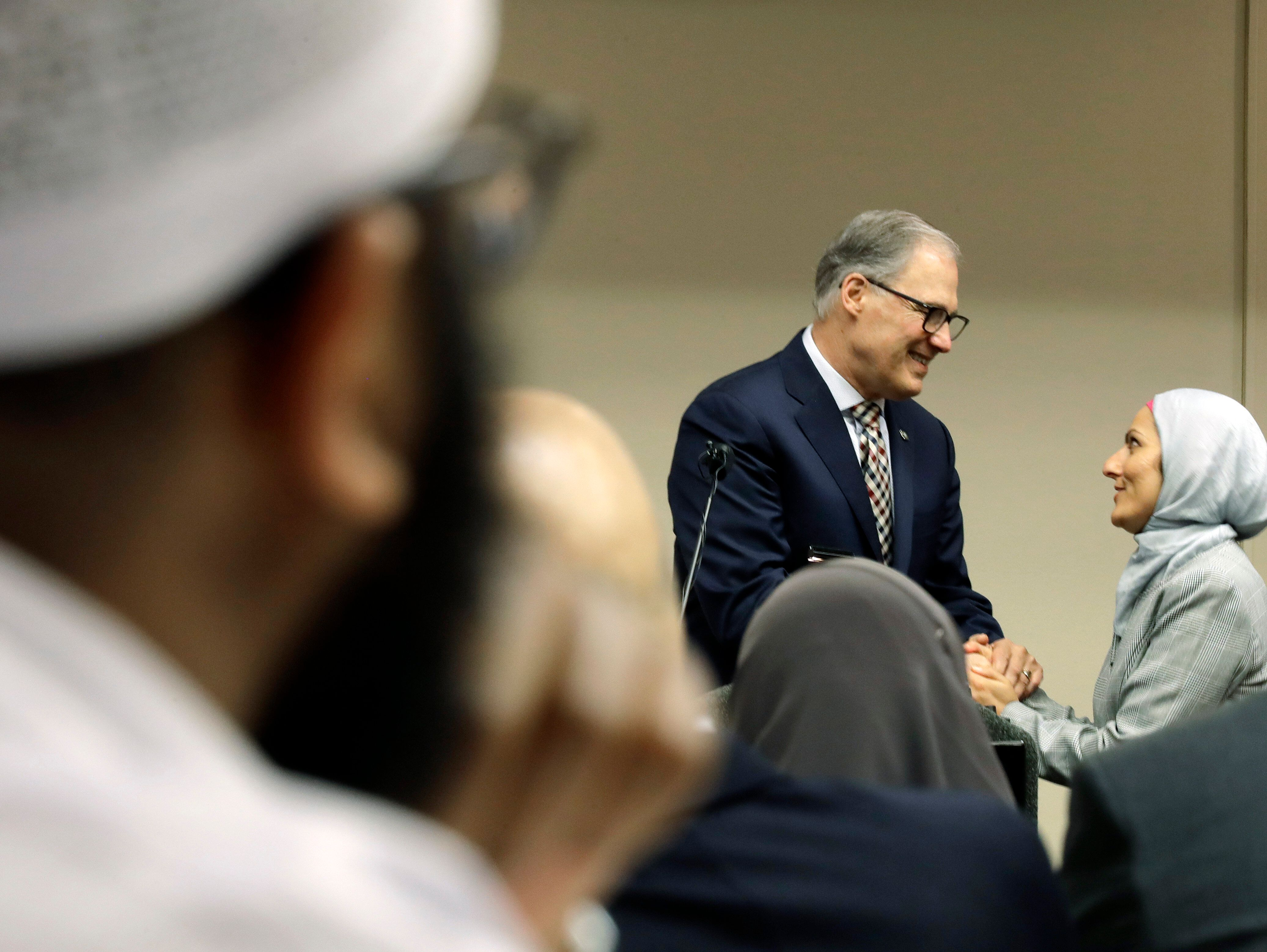Aneelah Afzali, right, executive director of the American Muslim Empowerment Network at the Muslim Association of Puget Sound, greets Washington Gov. Jay Inslee, center, during a session of Washington Muslim Day at the Capitol, which was organized by the Washington state chapter of the Council on American-Islamic Relations, Thursday, March 21, 2019, in Olympia, Wash. Attendees spent the day meeting with legislators, and heard speeches from Inslee and Lt. Gov. Cyrus Habib. (AP Photo/Ted S. Warren)