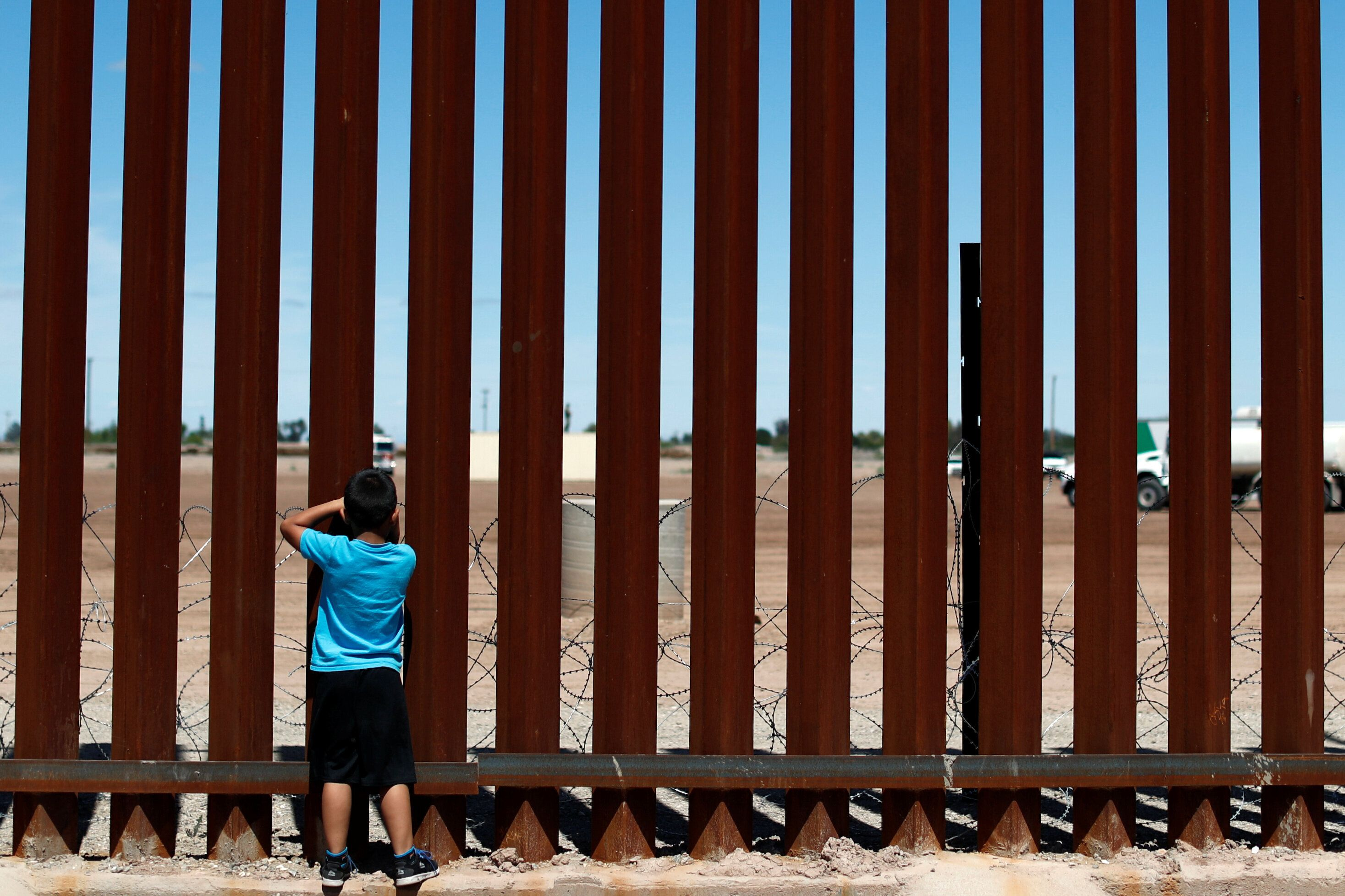A child looks through the border wall during the visit of U.S. President Donald Trump to Calexico, California, as seen in Mexicali, Mexico April 5, 2019. REUTERS/Carlos Jasso