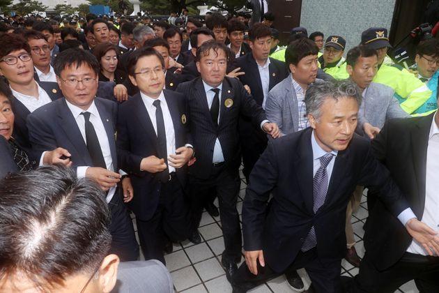 황교안 자유한국당 대표가 18일 광주 북구 국립5·18민주묘지에서 열린 제39주년 5·18민주화운동 기념식에 참석한 뒤 경호를 받으며 행사장을 빠져나가고