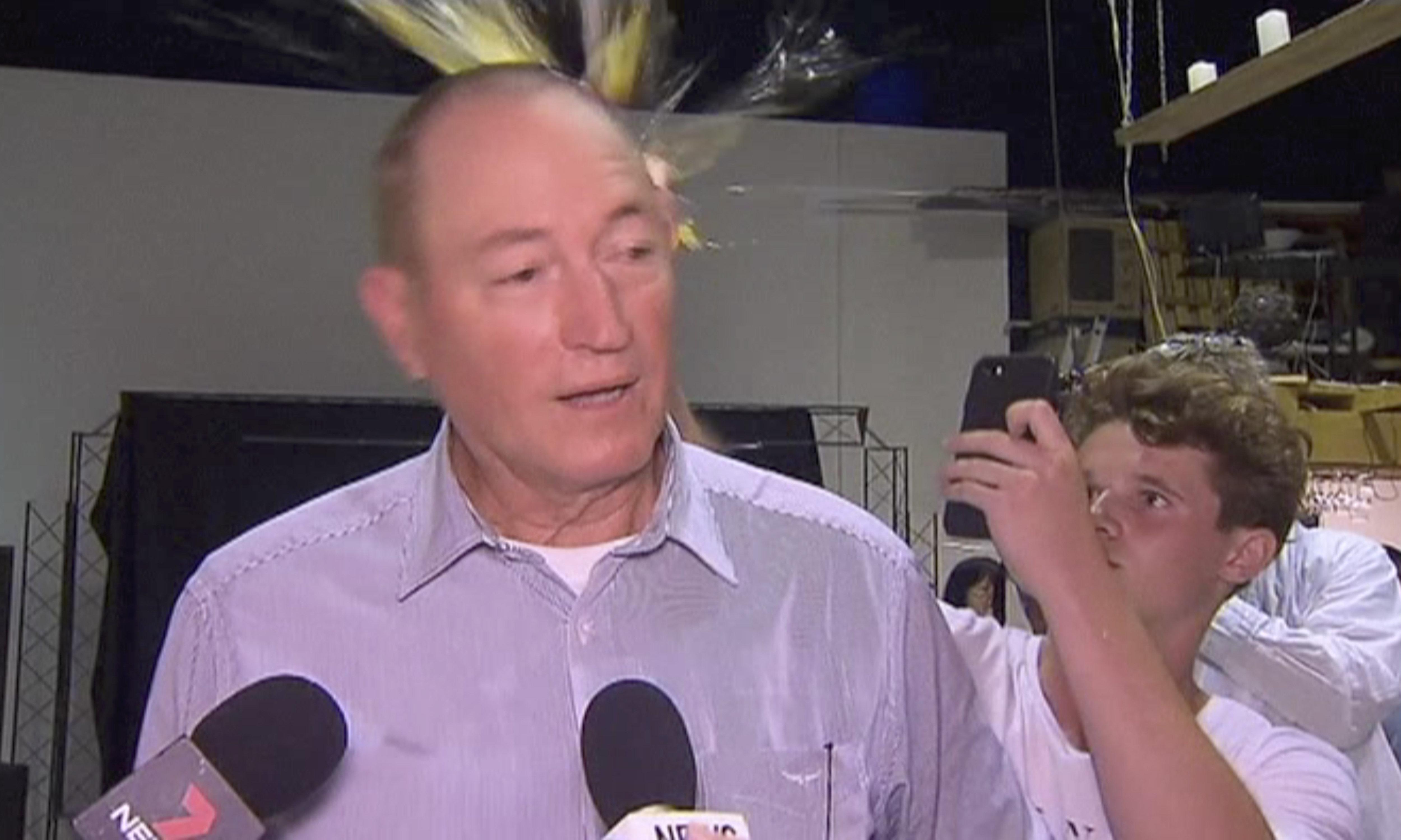En esta imagen tomada de un video, un adolescente rompe un huevo en la cabeza del senador Fraser Anning, durante una conferencia de prensa, el sábado 16 de marzo de 2019, en Melbourne, Australia. (AP Foto)