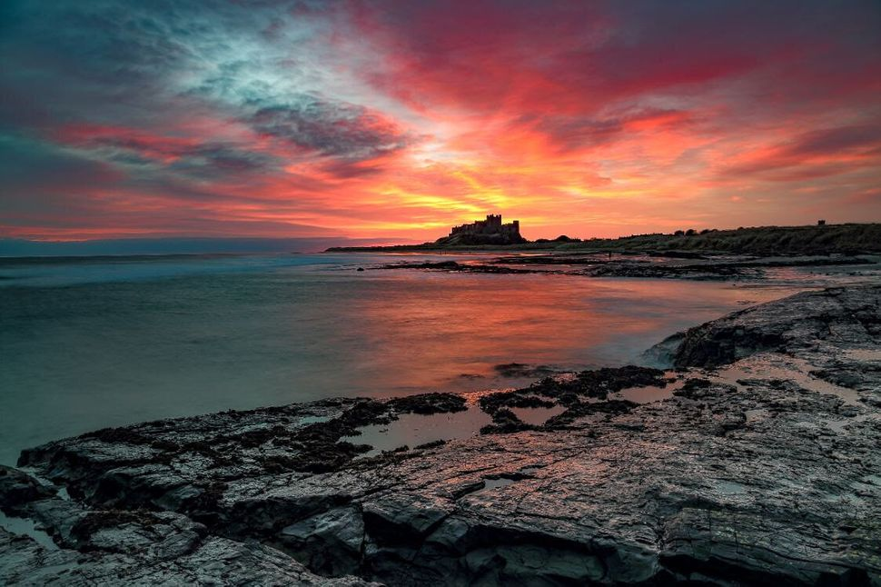 Sunrise explosion: A sunrise combined with low tide makes for a stunning image of Bamburgh Castle, Northumberland taken from the North Beach.