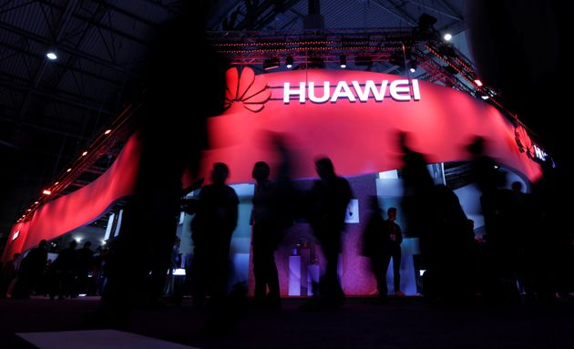 Visitors walk past Huawei's booth during Mobile World Congress in Barcelona, Spain, February 27,