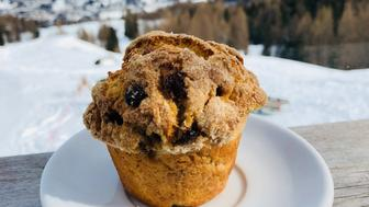 Blueberry muffin on a table at a rifugio in Cortina d'Ampezzo, with the Dolomites in the background