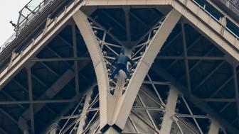 "TOPSHOT - A man (C) climbs up to the top of the Eiffel Tower, in Paris, without any protection, on May 20, 2019. - The Eiffel Tower was evacuated on May 20, 2019 in the afternoon after a person was spotted climbing up the Paris landmark, the company that operates the structure said. ""A climber has been spotted. It's the standard procedure: We have to stop the person, and in that case we evacuate the tower,"" an official told AFP, adding that police were on the scene. (Photo by FRANCOIS GUILLOT / AFP)        (Photo credit should read FRANCOIS GUILLOT/AFP/Getty Images)"