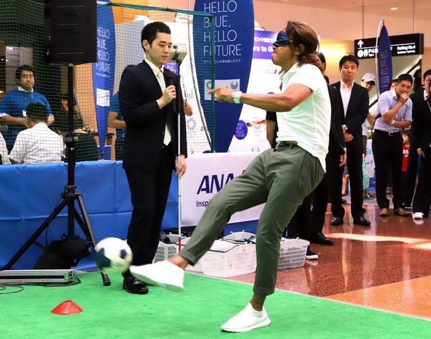 全日本空輸(ANA)の「東京2020パラリンピック競技大会開催『2年前』イベント」に出席した、漫談家の濱田祐太郎さん(中央)とサッカー元日本代表で日本障がい者サッカー連盟会長の北沢豪さん(同右)。ブラインドサッカーに挑戦した(東京都)
