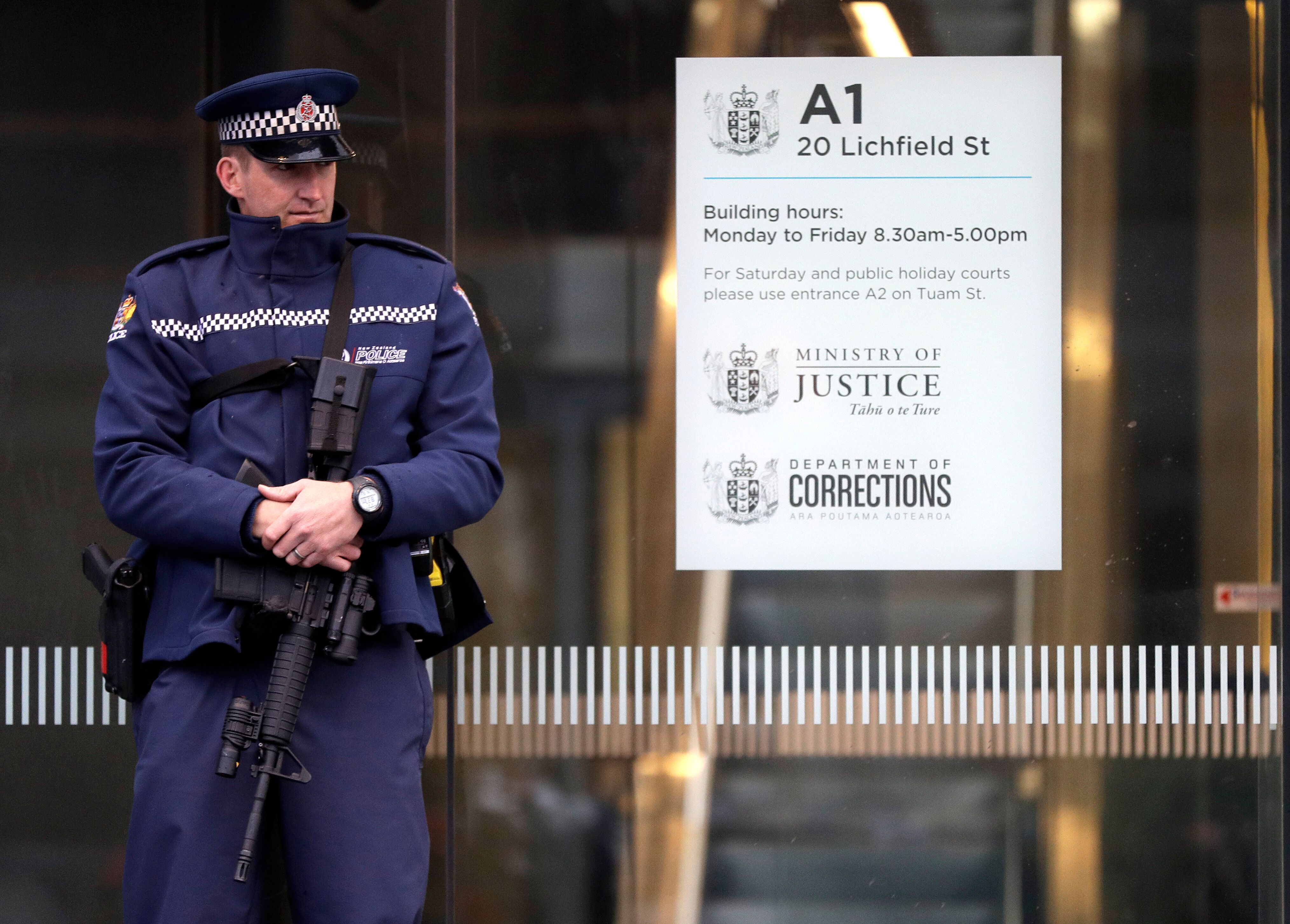 A armed police office stands guard outside the entrance to the High Court in Christchurch, New Zealand, Friday, April 5, 2019. A New Zealand judge has ordered that the man accused of killing 50 people at two New Zealand mosques, 28-year-old Brenton Harrison Tarrant, undergo two mental health tests to determine if he's fit to enter pleas in the case. (AP Photo/Mark Baker)