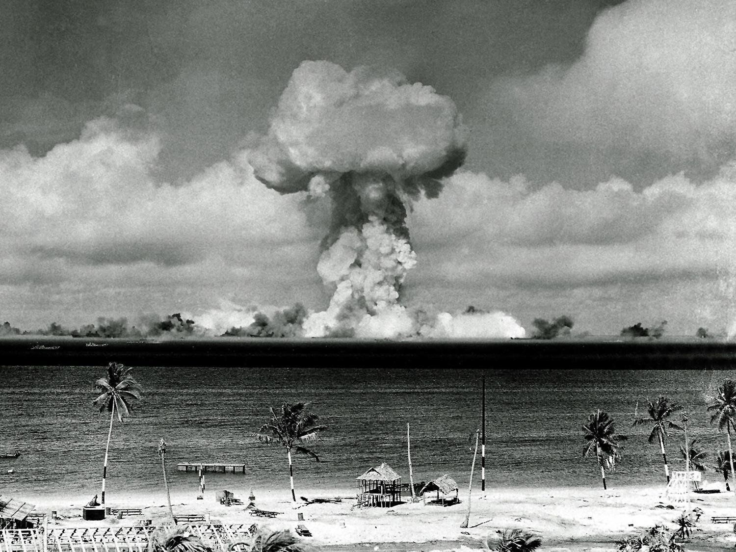 Mushroom cloud from atomic bomb explosion rises in Bikini lagoon, Marshall Islands, B&W photo on black