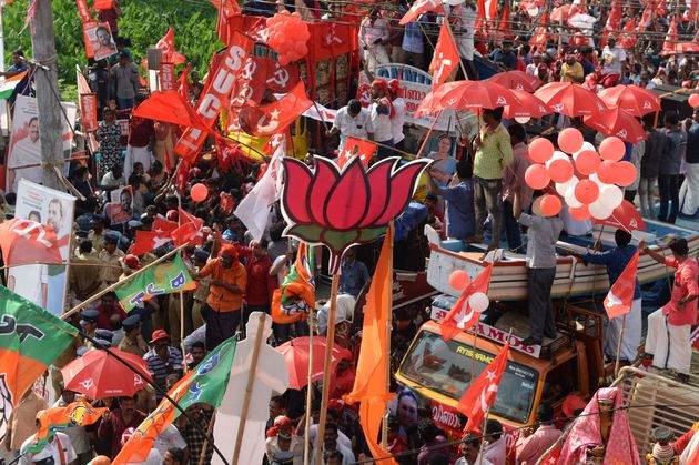 Supporters of BJP, Congress and CPI celebrate in front of each other during the final day of election...