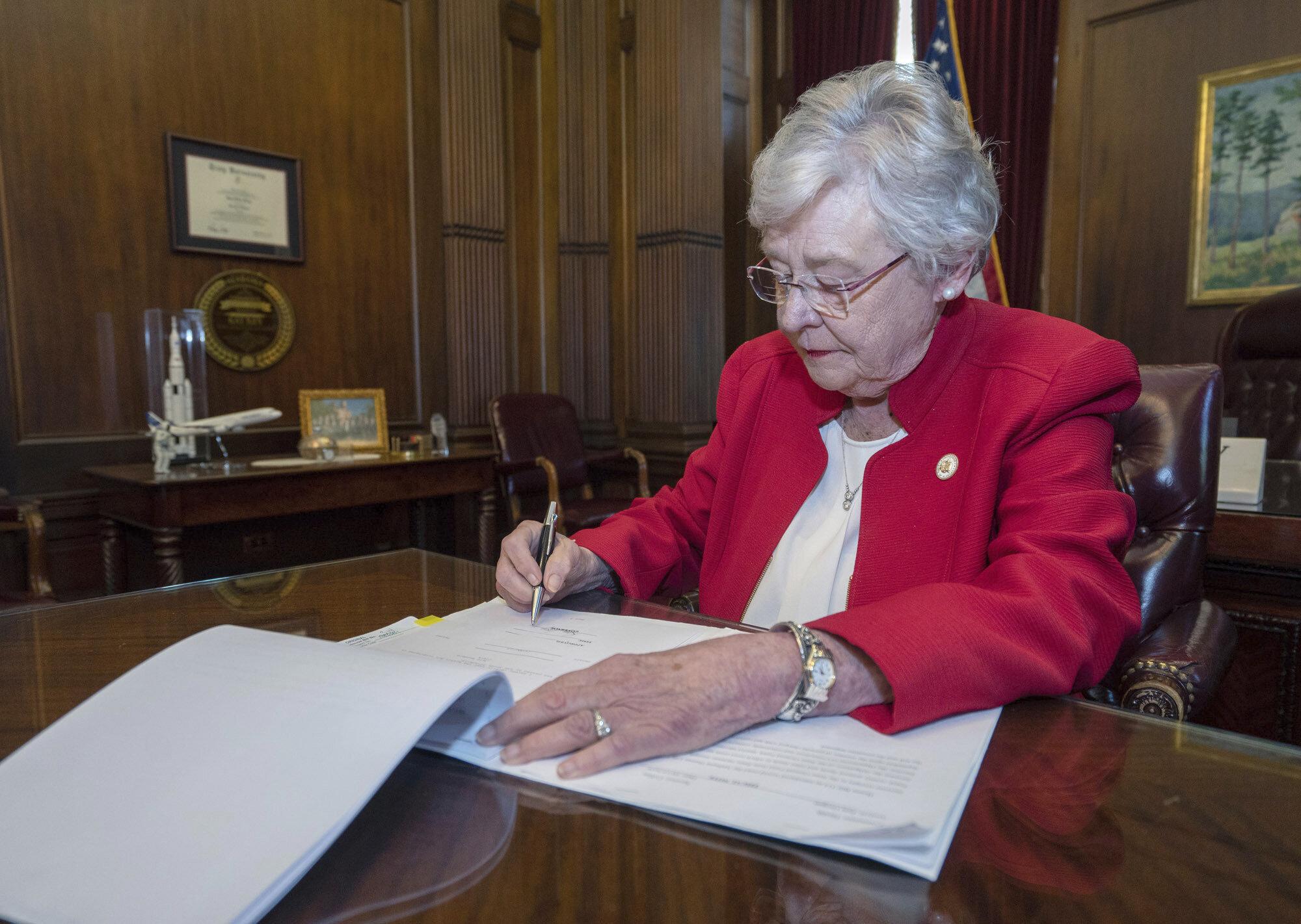 La gobernadora de Alabama, Kay Ivey, firma una ley que penaliza el aborto en casi todos los casos en el estado, el miércoles 15 de mayo de 2019, en Montgomery, Alabama. (Hal Yeager/Alabama Governor's Office vía AP)