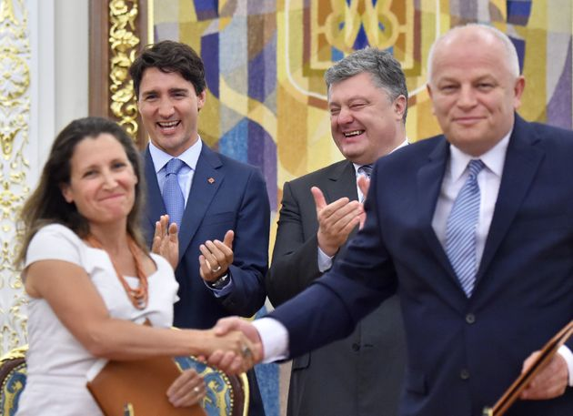 Former Ukrainian President Petro Poroshenko claps along with Prime Minister Justin Trudeau while...