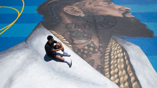 In this April 17, 2019 photo, mural artist Gustavo Zermeno Jr. poses for photos on a basketball court mural he dedicated to slain rapper Nipsey Hussle in Los Angeles. More than 50 colorful murals of Hussle have popped up in Los Angeles since the beloved rapper and community activist was gunned down outside his clothing store. (AP Photo/Jae C. Hong)