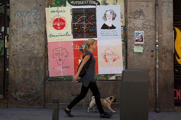 Una mujer pasea a su perro ante carteles de apoyo a Manuela Carmena, en