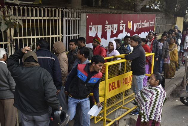 People queue up in front of Punjab National Bank to withdraw or deposit the money at Trilok Puri on December...