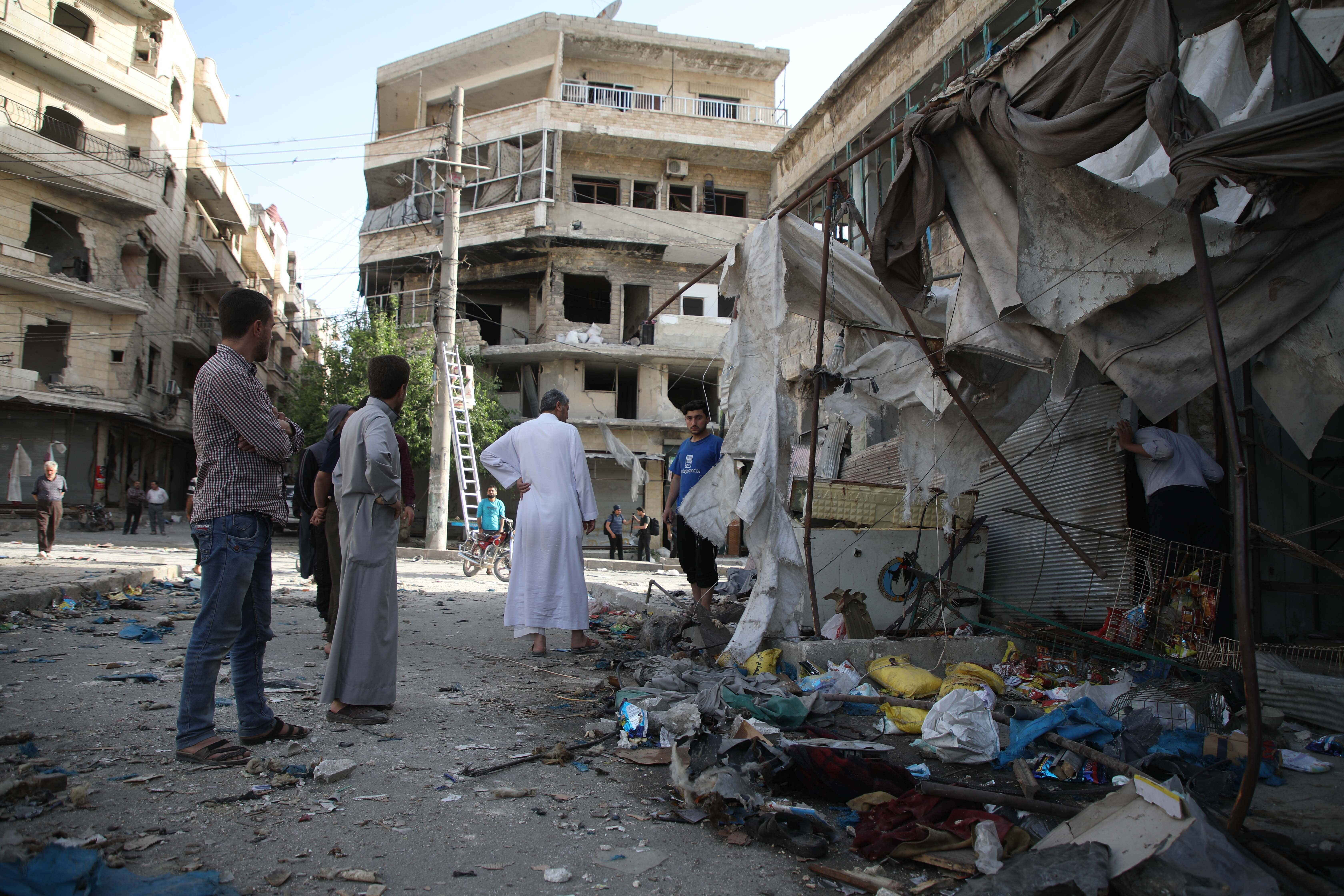 People gather at the site of an air strike on a market in the town of Maarat al-Numan on May 21, 2019. - At least 12 people were killed and 18 others wounded in overnight strikes on the Idlib  town of Maarat al-Numan, the Britain-based Syrian Observatory for Human Rights said. (Photo by Aaref WATAD / AFP)        (Photo credit should read AAREF WATAD/AFP/Getty Images)