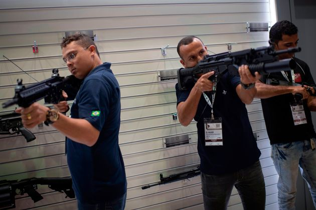 Visitantes seguram fuzis durante a feira de Defesa e Segurança LAAD no Rio em