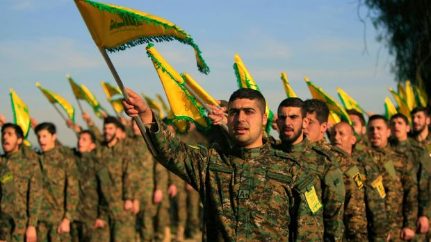 FILE - In this Feb. 13, 2016 file photo, Hezbollah fighters hold flags as they attend the memorial of their slain leader Sheik Abbas al-Mousawi, who was killed by an Israeli airstrike in 1992, in Tefahta village, south Lebanon. U.S. Secretary of State Mike Pompeo's visit to Lebanon this week is expected to underscore the Trump administration's displeasure with Hezbollah's growing influence in Lebanese politics. The Iranian-backed group wields more power than ever in the country's Cabinet and parliament. (AP Photo/Mohammed Zaatari, File)
