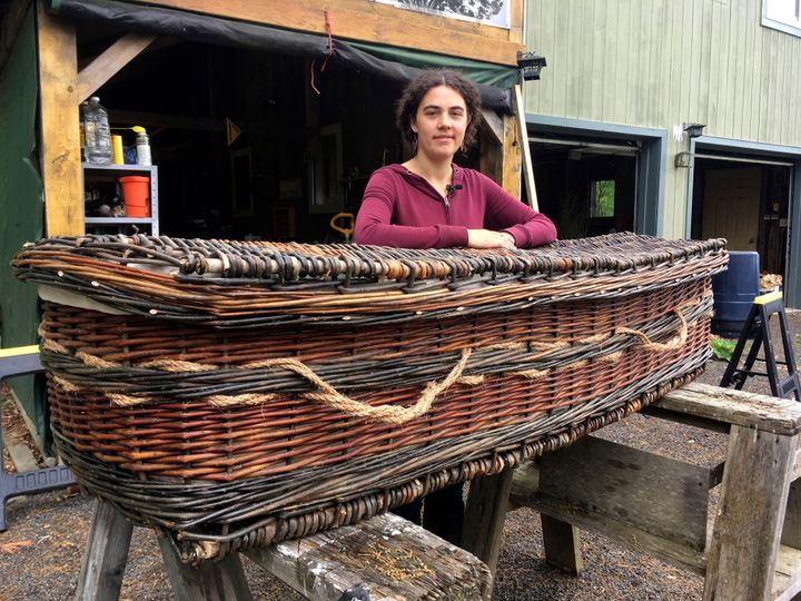 Mary Lauren Fraser stands beside a biodegradable casket she hand-wove from willow, in Montague, Massachusetts.