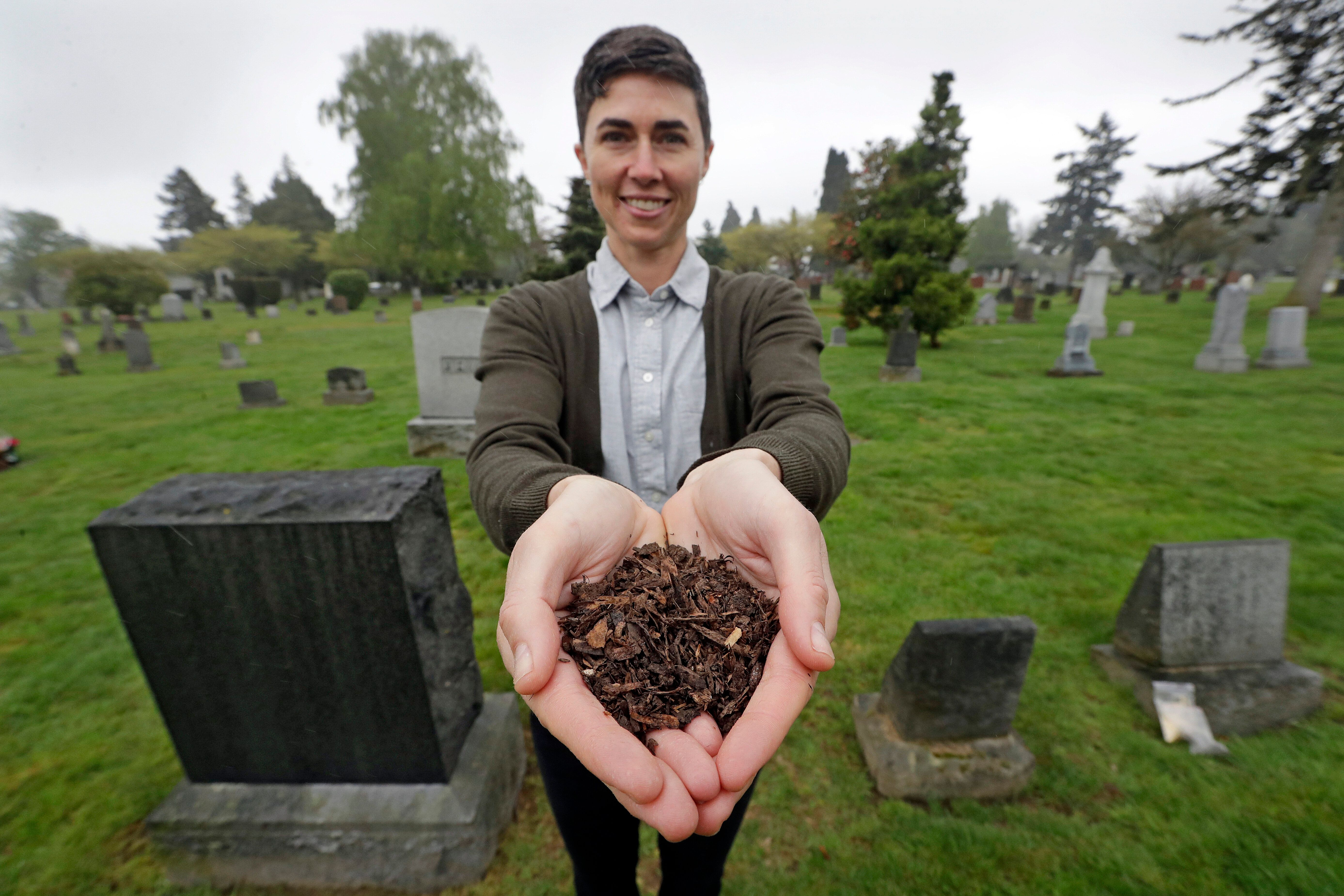 """FILE - In this April 19, 2019, file photo, Katrina Spade, the founder and CEO of Recompose, a company that hopes to use composting as an alternative to burying or cremating human remains, poses for a photo in a cemetery in Seattle, as she displays a sample of compost material left from the decomposition of a cow using a combination of wood chips, alfalfa and straw. On Tuesday, May 21, 2019, Washington Gov. Jay Inslee signed a bill into law that allows licensed facilities to offer """"natural organic reduction,"""" which turns a body, mixed with substances such as wood chips and straw, into soil in a span of several weeks. Th law makes Washington the first state in the U.S. to approve composting as an alternative to burying or cremating human remains. (AP Photo/Elaine Thompson, File)"""
