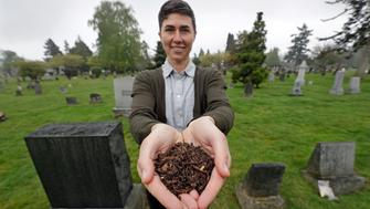 "FILE - In this April 19, 2019, file photo, Katrina Spade, the founder and CEO of Recompose, a company that hopes to use composting as an alternative to burying or cremating human remains, poses for a photo in a cemetery in Seattle, as she displays a sample of compost material left from the decomposition of a cow using a combination of wood chips, alfalfa and straw. On Tuesday, May 21, 2019, Washington Gov. Jay Inslee signed a bill into law that allows licensed facilities to offer ""natural organic reduction,"" which turns a body, mixed with substances such as wood chips and straw, into soil in a span of several weeks. Th law makes Washington the first state in the U.S. to approve composting as an alternative to burying or cremating human remains. (AP Photo/Elaine Thompson, File)"