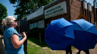 An anti-abortion protester shouts her as a woman is escorted by Clinic Escorts into the Reproductive Health Services building in Montgomery, Alabama, on May 20, 2019. - Abortion is among the most divisive political issues in the US, and the doorsteps of abortion clinics nationwide have become the sites of daily standoffs between pro- and anti-abortion rights activists. On the one side are activists who stake out clinics and attempt to convince women not to have abortions with tactics that reproductive rights advocates say are aggressive and involve harassment or shaming. (Photo by Seth HERALD / AFP)        (Photo credit should read SETH HERALD/AFP/Getty Images)