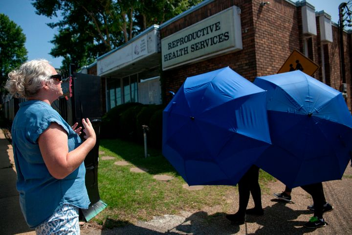 An anti-abortion protester shouts as a woman is escorted into the Reproductive Health Services building in Montgomery, Alabam