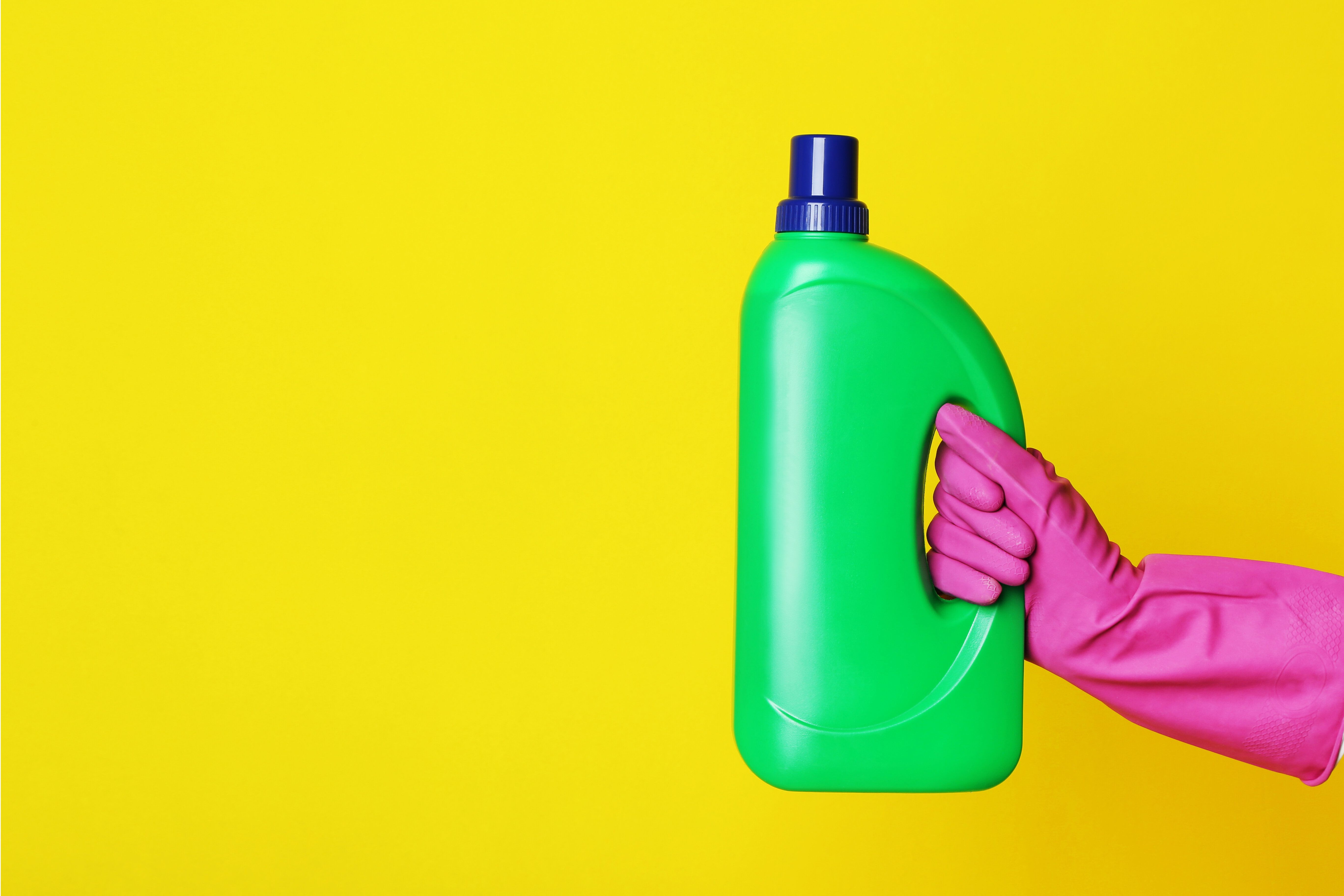 Female hand holding bottle with detergent on yellow background