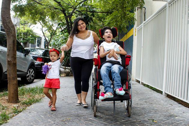 Adenilda Ramos da Silva, with her children: Jennifer, 21, who has cerebral palsy, and Lorena,