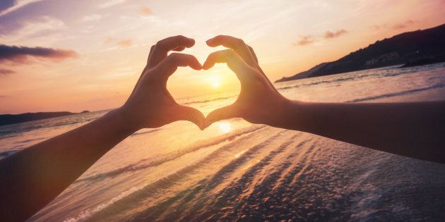 Couple formed heart shape with their hands against sunset over the