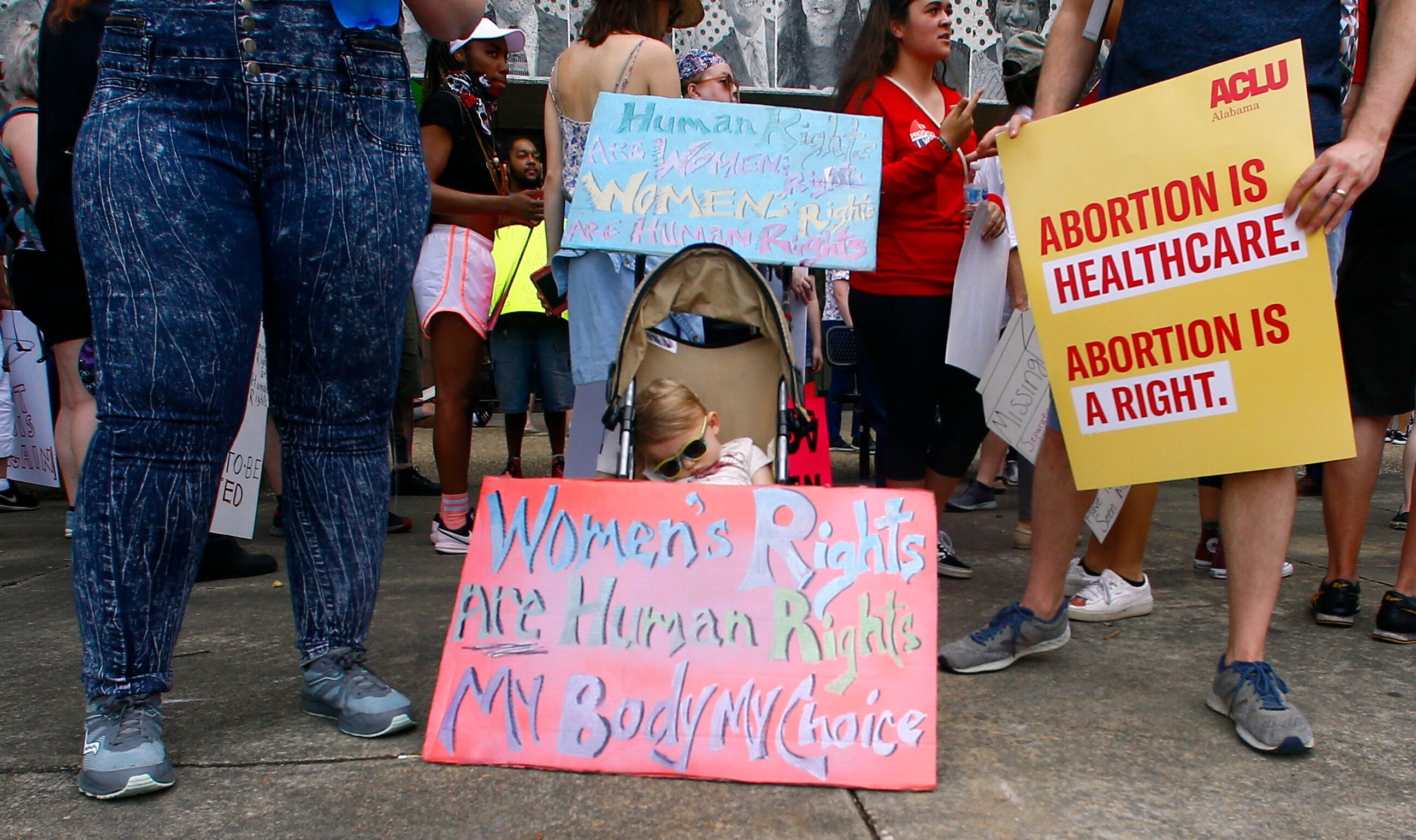 Owen Austin sleeps in his stroller while his parents wait with other protesters for women's rights to protest a law passed last week making abortion a felony in nearly all cases with no exceptions for cases of rape or incest, Sunday, May 19, 2019, in Montgomery, Ala. (AP Photo/Butch Dill)