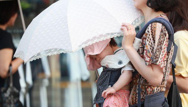 대구·경북 일부 지역에 올해 첫 폭염주의보가 발효된 5월 23일 오후 양산을 쓴 시민들이 거리를 지나고 있다.