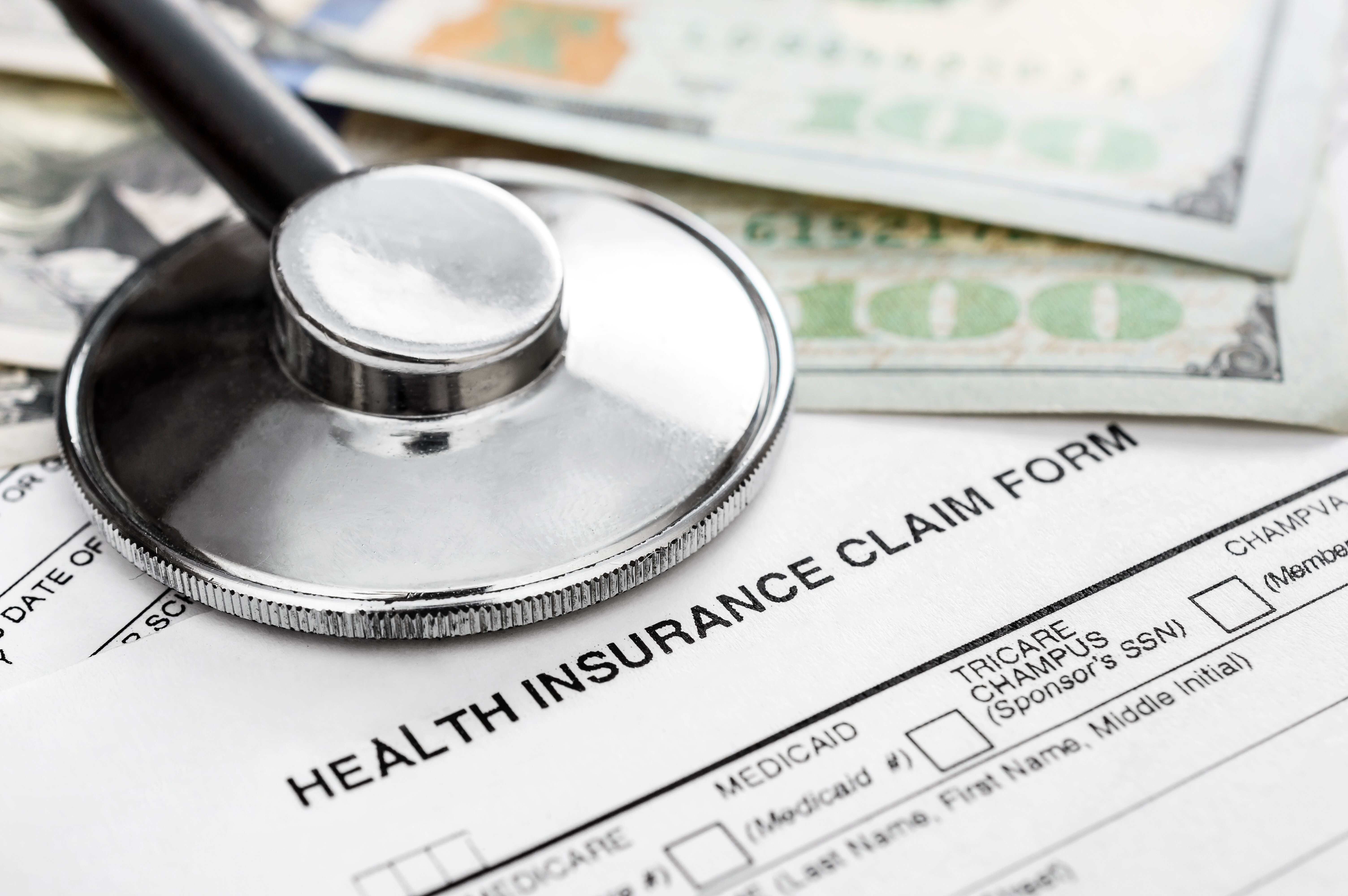 Stethoscope with money on health insurance claim form.