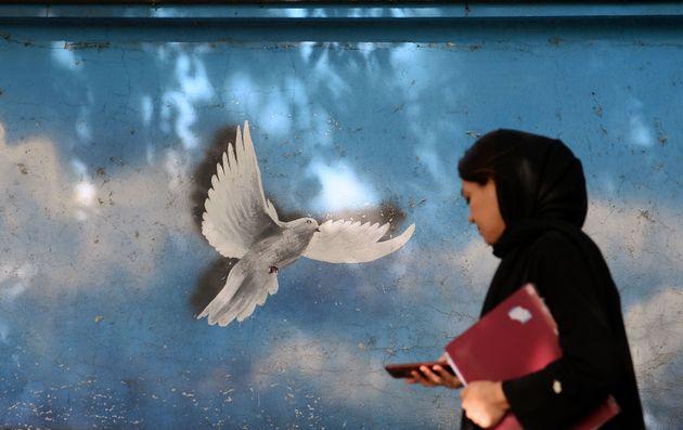 Una mujer pasa por delante de un mural en una calle de