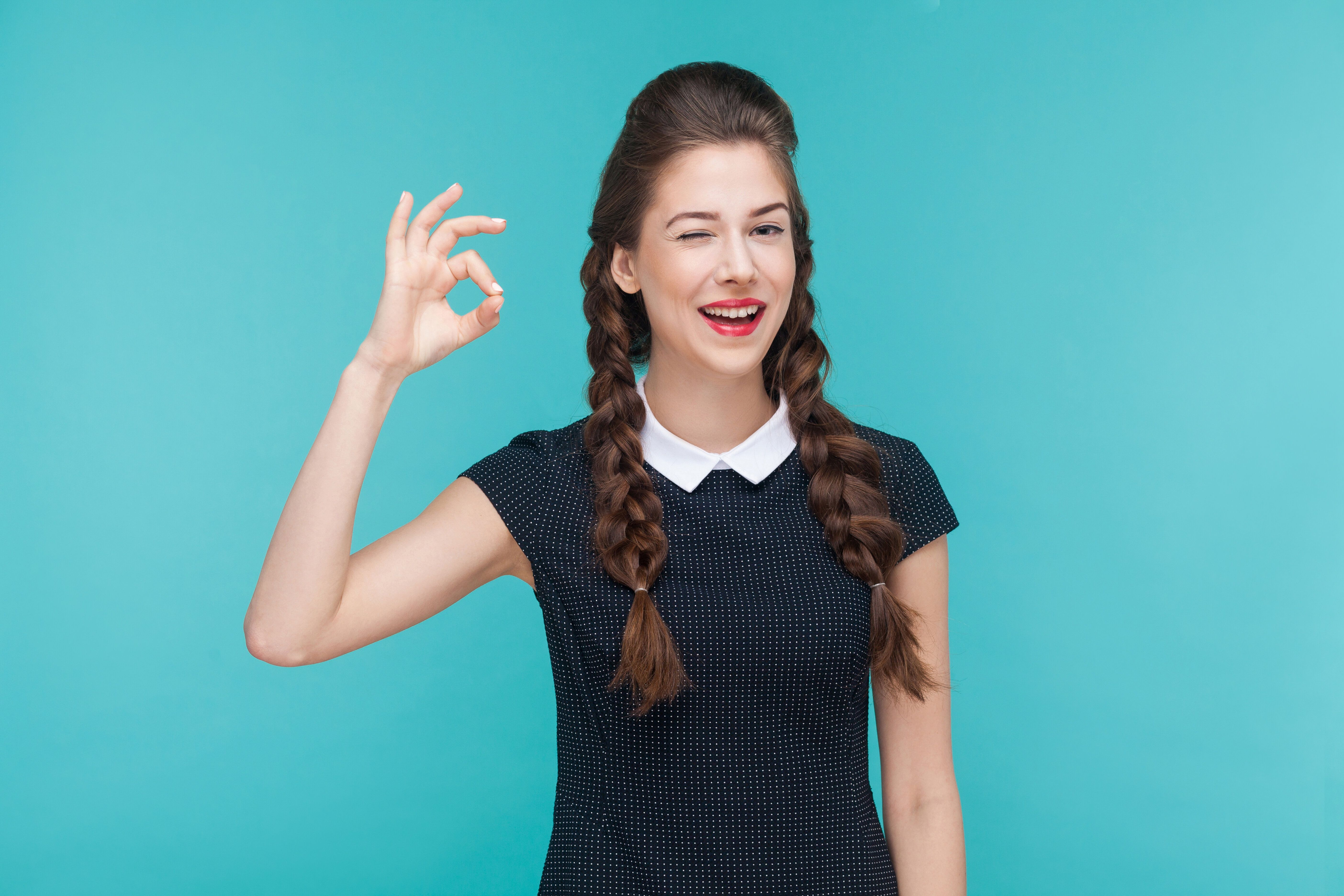 Gesture woman toothy smile and showing ok sign at camera. Indoor, studio shot on blue background