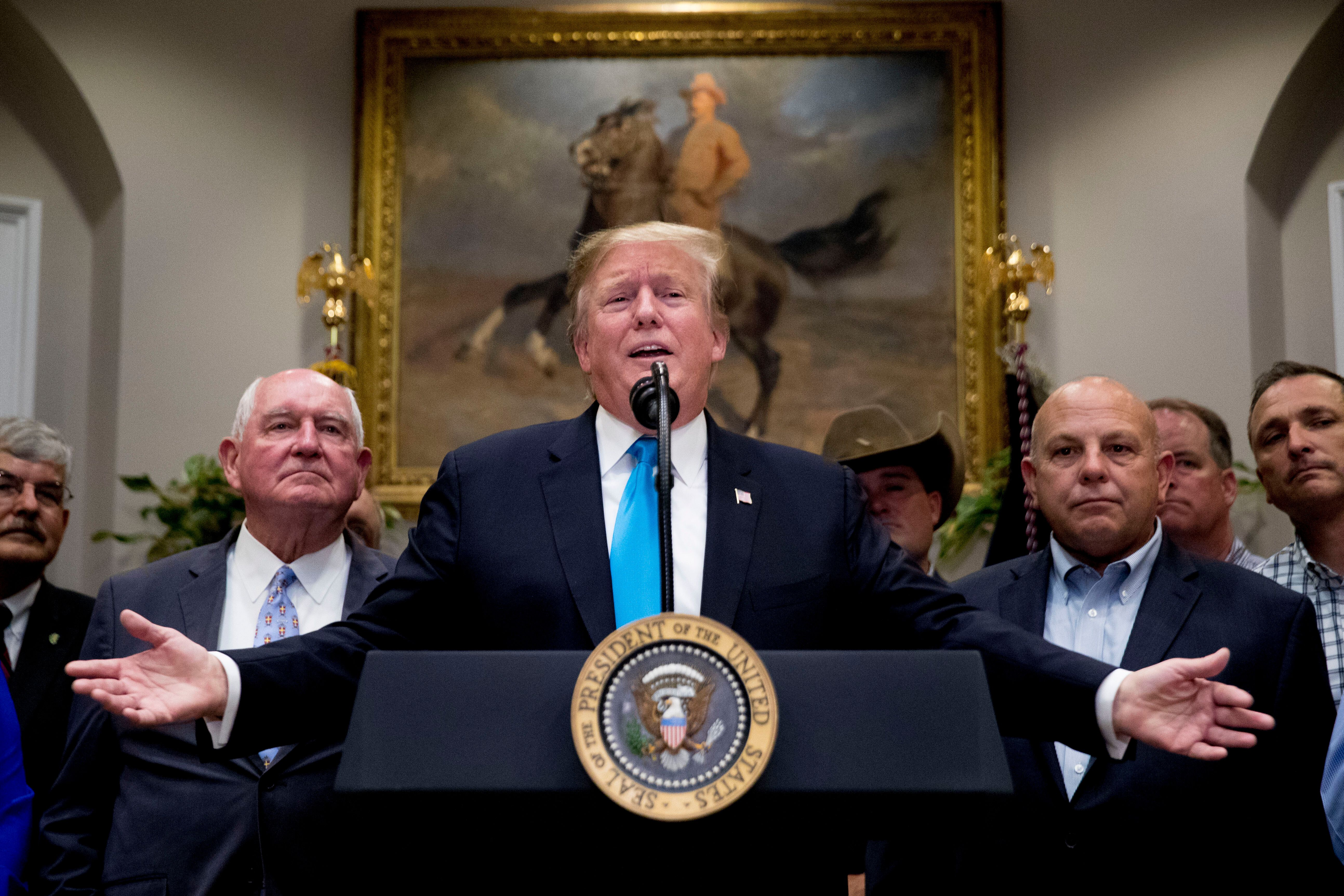 President Donald Trump, accompanied by Agriculture Secretary Sonny Perdue, left, gestures as he answers a question from a reporter during a meeting to support America's farmers and ranchers in the Roosevelt Room of the White House, Thursday, May 23, 2019, in Washington. (AP Photo/Andrew Harnik)