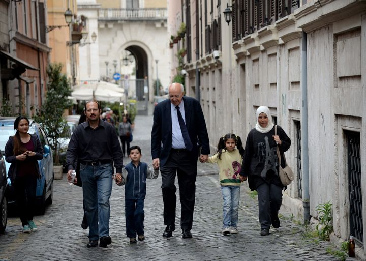 A family of Syrian refugees, part of a group of asylum seekers Pope Francis helped resettle, walks with a member of a Catholi