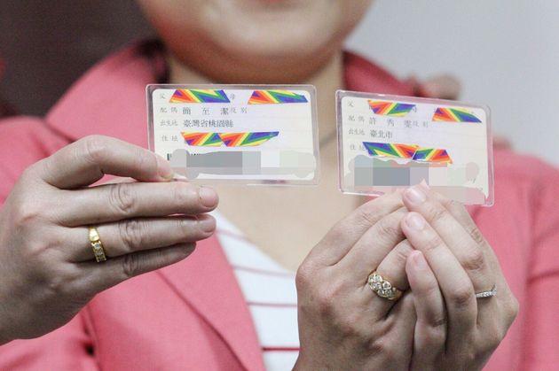 IDカードを手にする許秀雯さんと簡至潔さん。台湾では14歳以上の市民は、父親や母親、配偶者、居住地などの情報が書かれたIDカードを持つ。