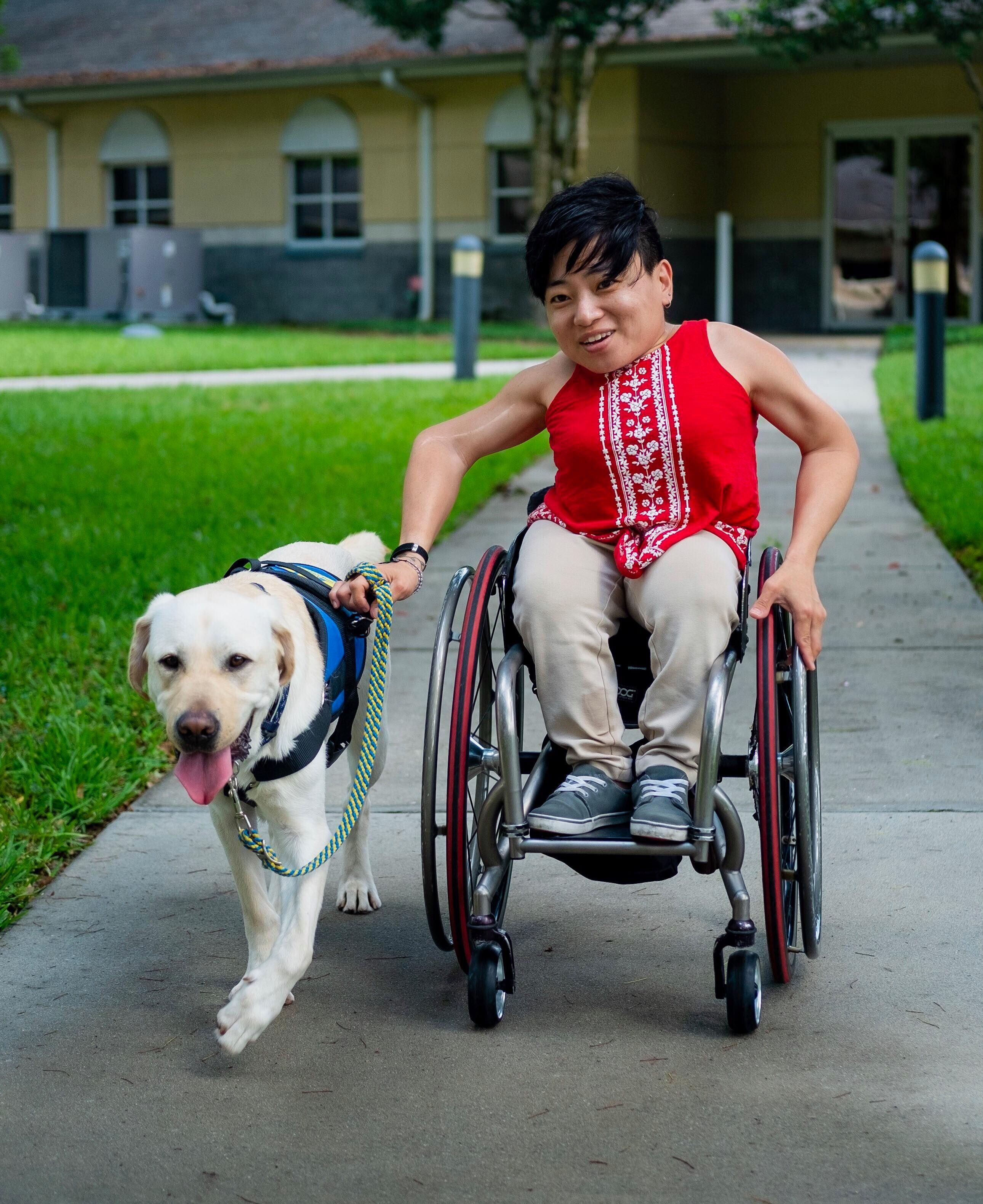 Mia Ives-Rublee is wearing a red tank top and sitting in a wheelchair, with her service dog walking next to her.