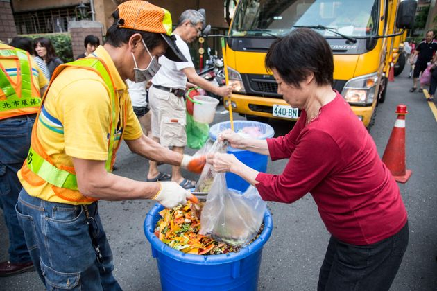 A city garbageman helps a resident dispose of food waste in
