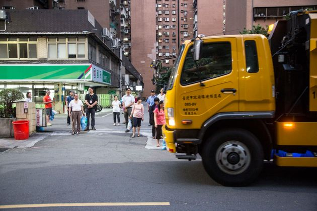 Taipei residents wait with their garbage for the trash collection trucks to arrive. Different trucks...