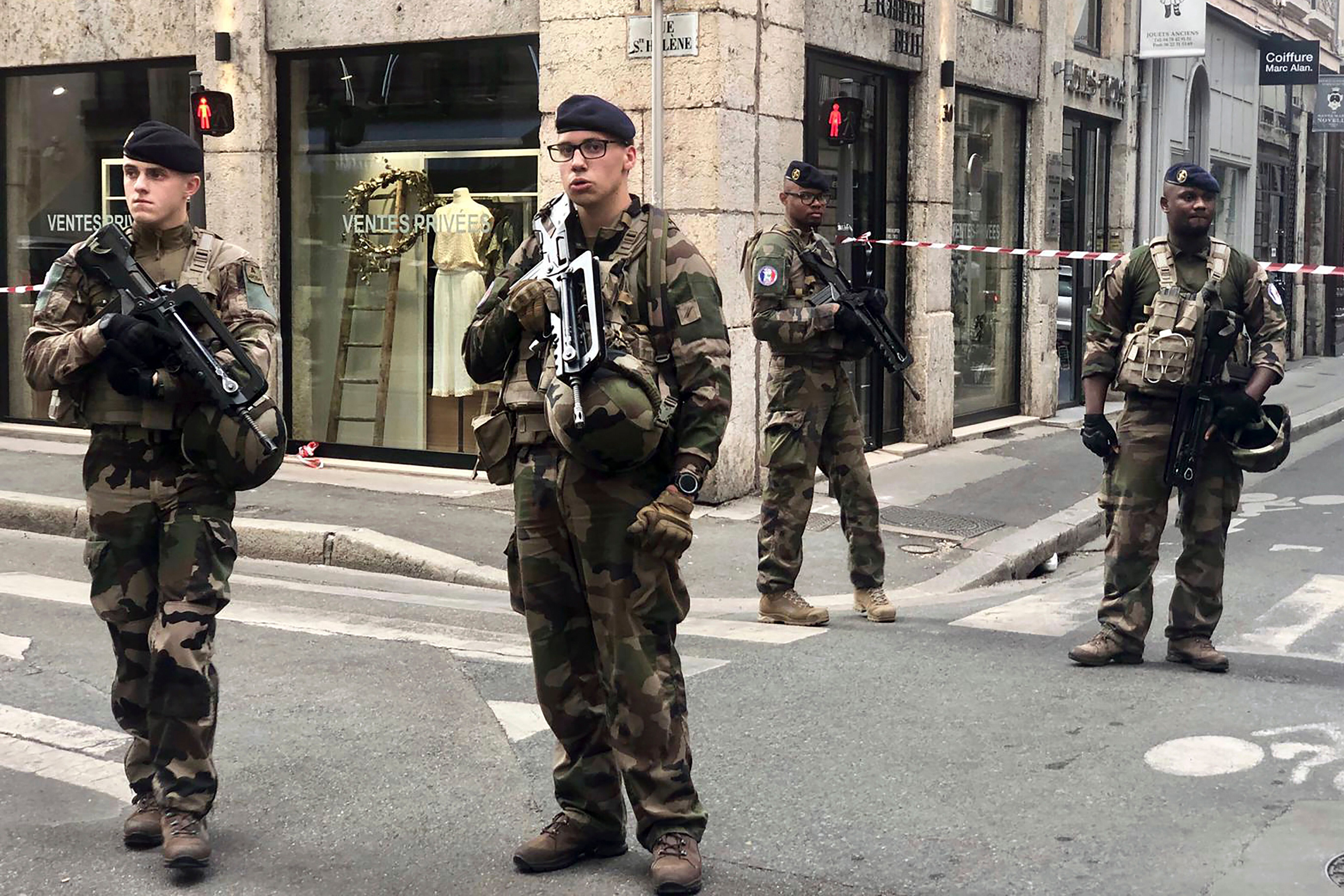 "Soldiers of French antiterrorist plan ""Vigipirate Mission"", secure the access near the site of a suspected bomb attack in central Lyon, Friday May, 24, 2019. A small explosion Friday on a busy street in the French city of Lyon lightly injured several people, local officials said. (AP Photo/Sebastien Erome)"