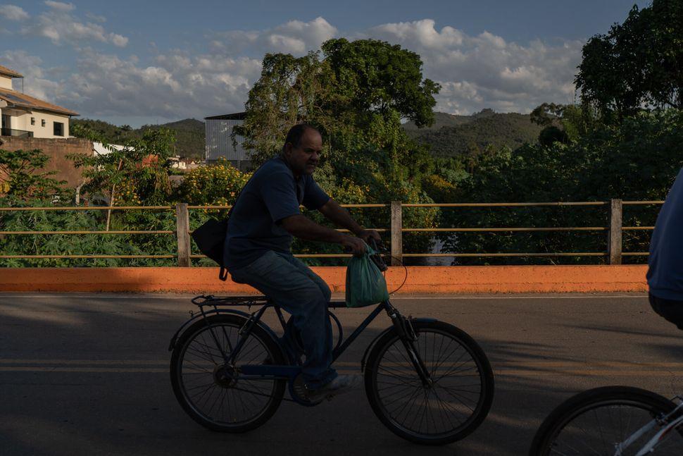 Homem percorre de bicicleta ponte sobre o rio São João, também marcada com tinta
