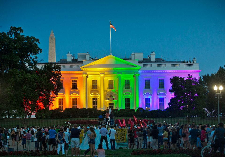 In this June 26, 2015, file photo, people gather in Lafayette Park to see the White House illuminated...