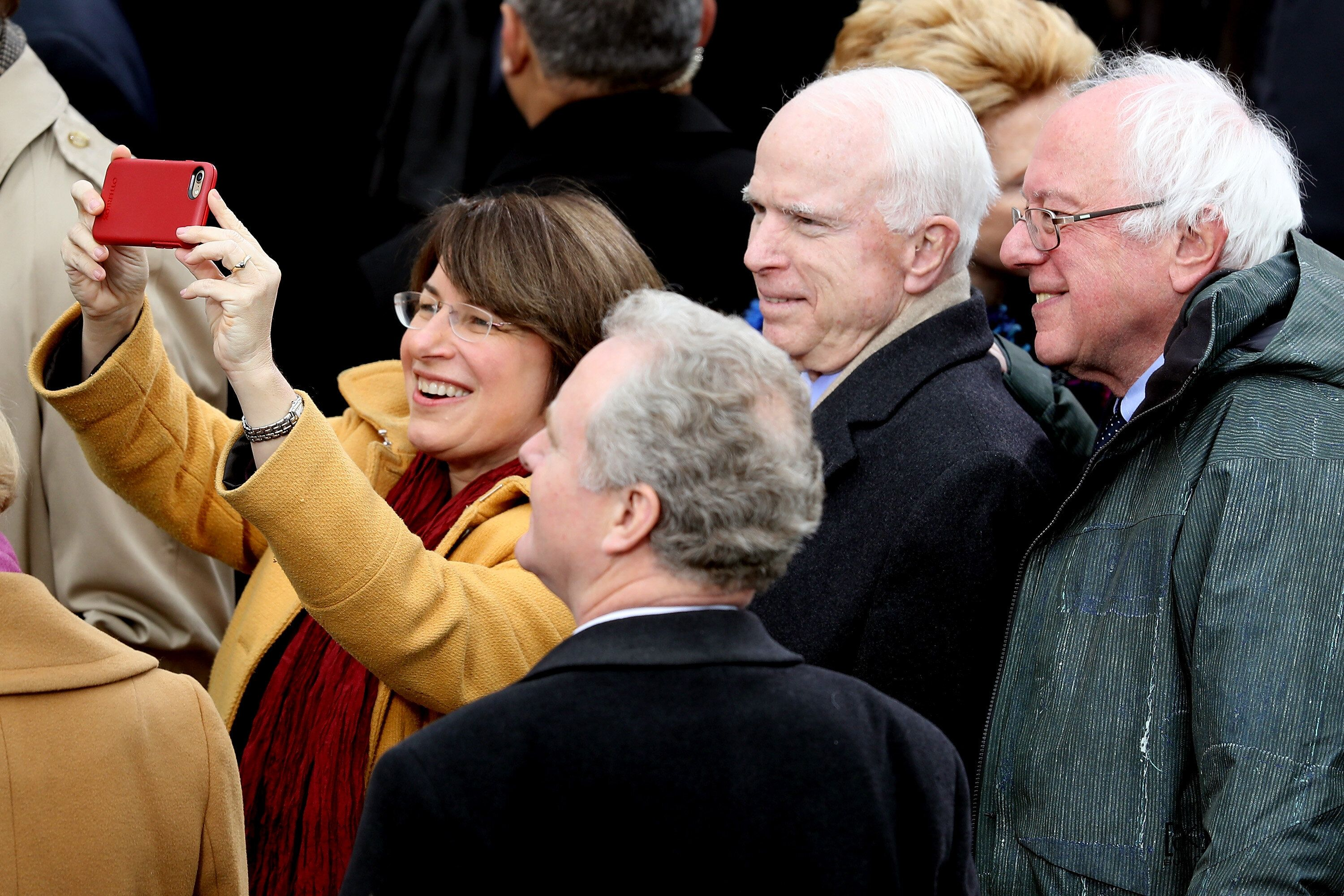 WASHINGTON, DC - JANUARY 20: (L-R) Sen. Amy Klobuchar (D-MN) (L) takes a selfie with Sen. Chris Van Hollen (D-MD), Sen. John McCain (R-AZ) and Sen. Bernie Sanders (D-VT) (R) on the West Front of the U.S. Capitol on January 20, 2017 in Washington, DC. In today's inauguration ceremony Donald J. Trump becomes the 45th president of the United States.  (Photo by Joe Raedle/Getty Images)