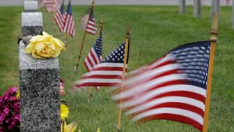 Rain drops stand out on a yellow rose as flags flutter in the wind next to the gravestone of Oliver Hickles, who served in World War II and Korea in the U.S. Army, at Tahoma National Cemetery, Friday, May 24, 2019, in Kent, Wash. Monday is Memorial Day, a U.S. federal holiday to honor those who died while serving in the military. (AP Photo/Ted S. Warren)